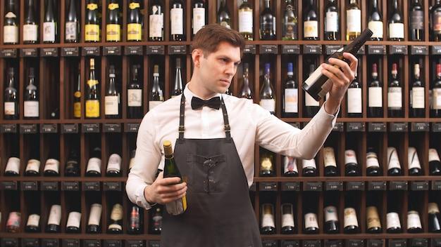 Lindo vendedor de vino tiene botellas de vino y lee la etiqueta en una tienda de vinos. te ayuda a elegir