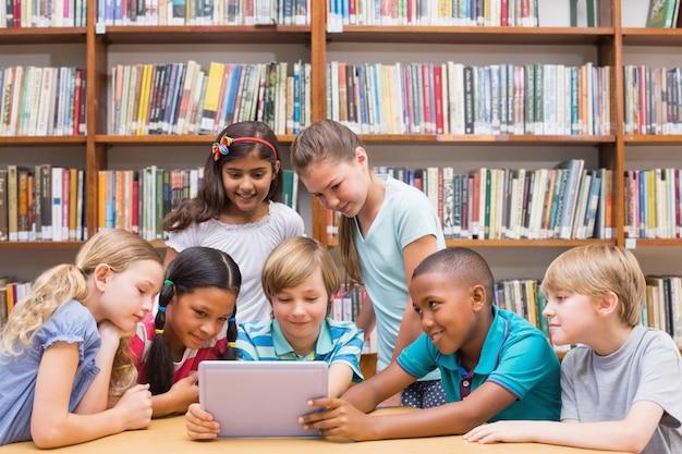Lindos alumnos usando la tableta en la biblioteca