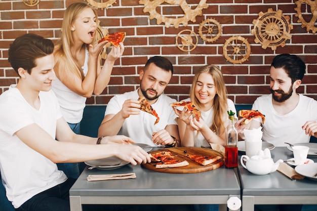 Lindos amigos en una cafetería comiendo una pizza