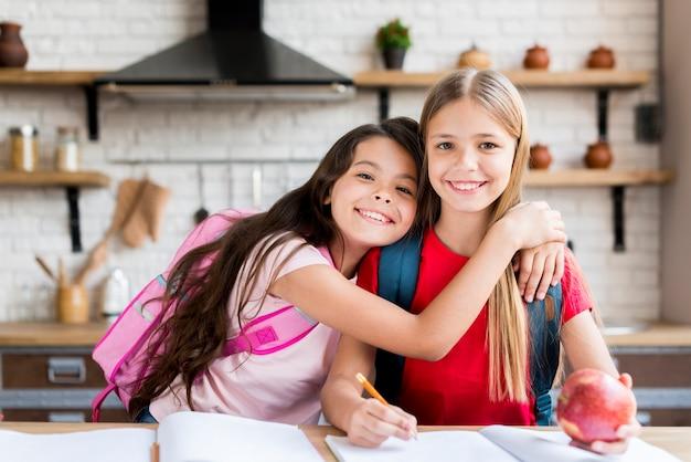 Lindos escolares con mochilas sentados en la mesa y haciendo la tarea en casa