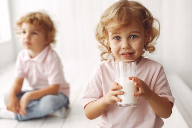 Lindos niños bebiendo leche en casa
