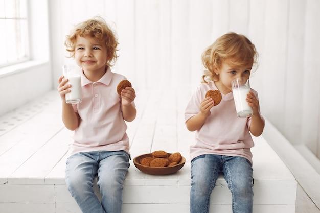 Lindos niños comiendo galletas y bebiendo leche