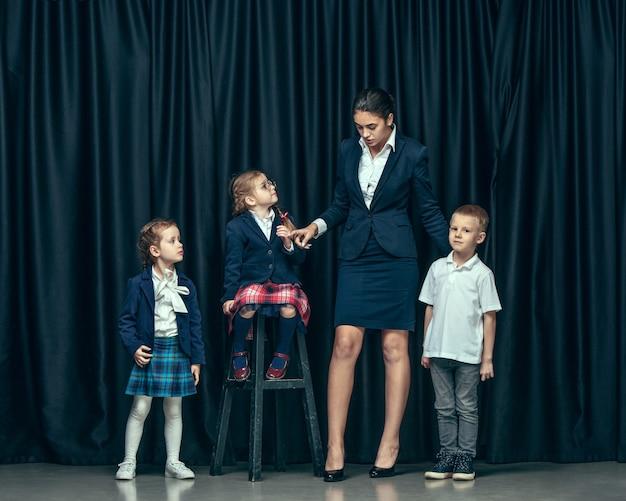 Lindos niños con estilo sobre fondo oscuro de estudio. las hermosas adolescentes y el niño parados juntos
