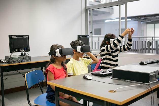 Lindos niños multiétnicos aprendiendo a usar gafas de realidad virtual