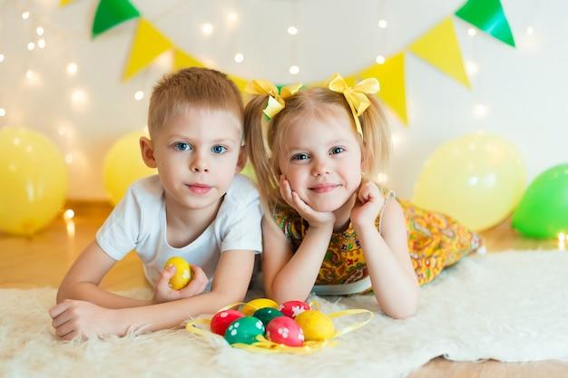 Lindos niños pequeños de 3 a 5 años de edad se acuestan boca abajo, en el piso con ropas brillantes con huevos de pascua