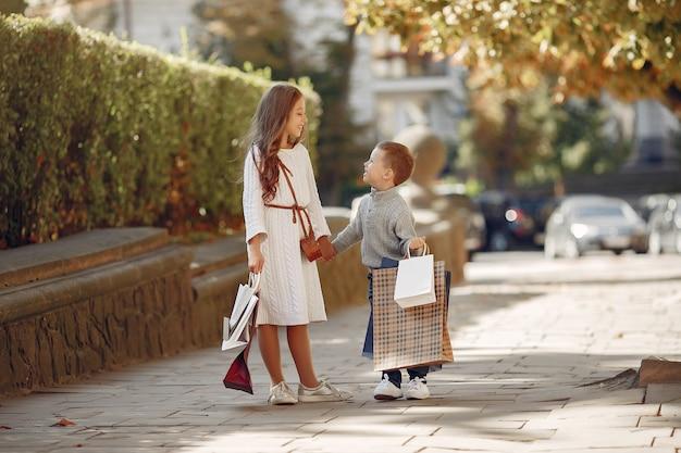 Lindos niños pequeños con bolsa de compras en una ciudad