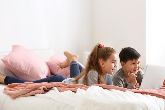 Lindos niños pequeños con laptop viendo dibujos animados en casa