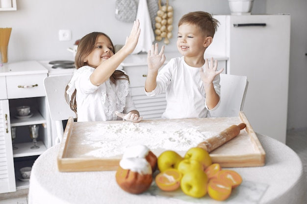 Lindos niños pequeños sentados en una cocina con masa
