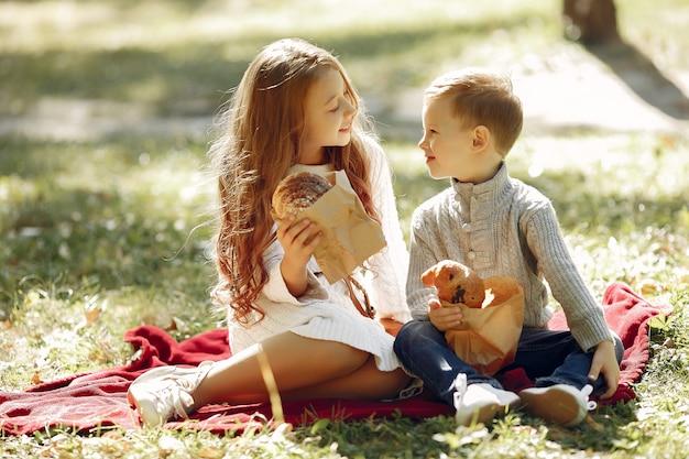 Lindos niños pequeños sentados en un parque con pan