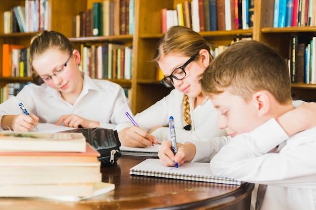 Lindos niños que estudian en la biblioteca de la escuela