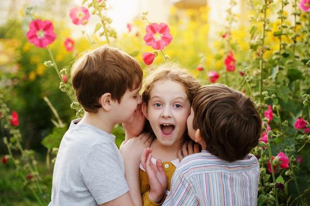 Lindos niños susurran en verano al aire libre.