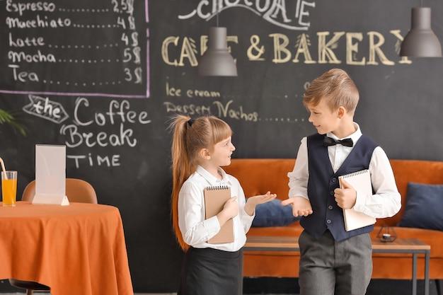 Lindos pequeños camareros en el restaurante
