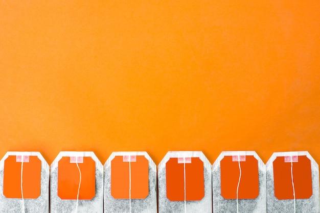 Línea de bolsitas de té naranja brillante con té orgánico a base de hierbas dentro sobre fondo naranja
