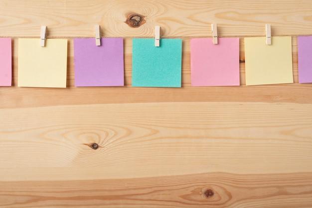 Línea de coloridas notas adhesivas en una cuerda con alfileres de ropa