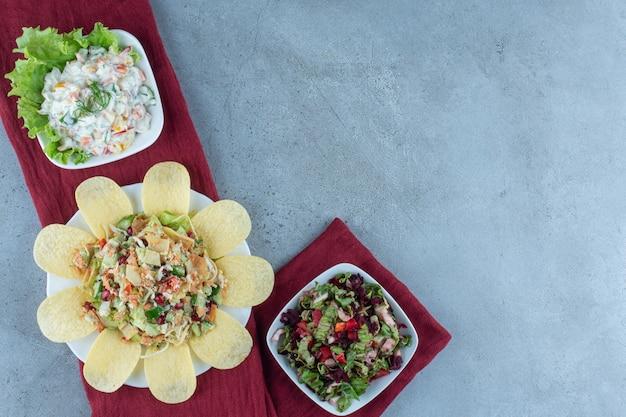 Línea de ensaladas variadas adornadas con hojas de lechuga y patatas fritas sobre mármol.