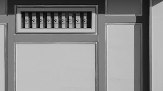 Línea de escultura en bajo relieve en pared de madera gris con sombra.