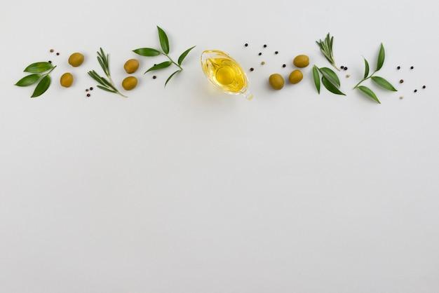 Línea de hojas y aceitunas con taza de aceite.