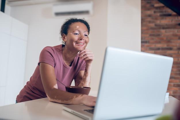 En línea. joven mulata en la cocina viendo algo en internet y sonriendo