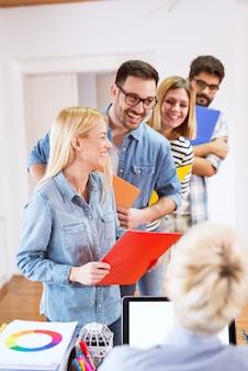 Línea de jóvenes atractivos seguros de pie con carpetas frente al jefe para la entrevista.