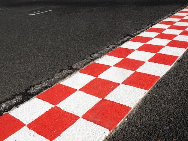 Línea de meta en pista de carreras, color rojo y blanco.
