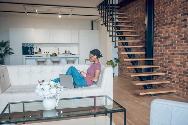 En línea. una mujer en ropa casual navegando por internet mientras descansa en casa