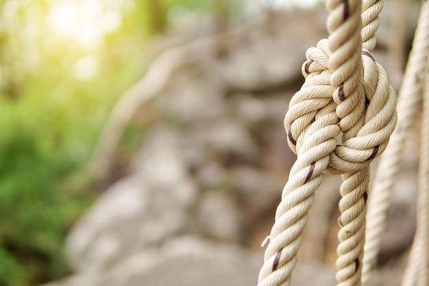 Línea de nudo de cuerda atada con fondo de piedra borrosa