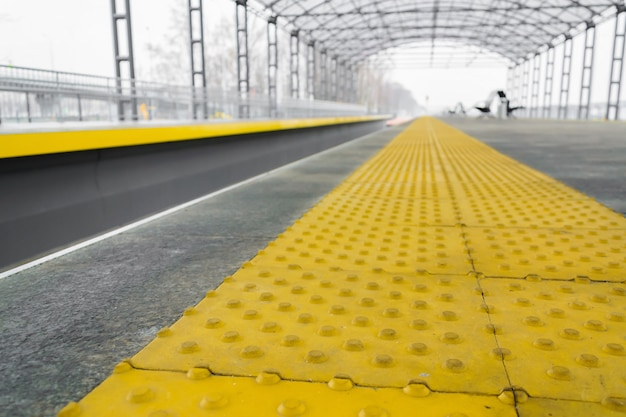 Línea de parada amarilla para personas ciegas en la estación de ferrocarril en perspectiva