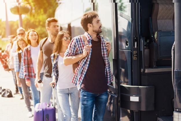 Línea de personas cola de turistas que toman un autobús.