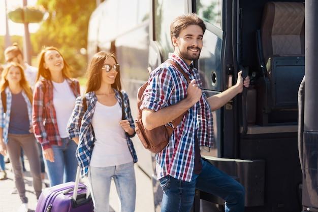 Línea de personas felices turistas están tomando un autobús.