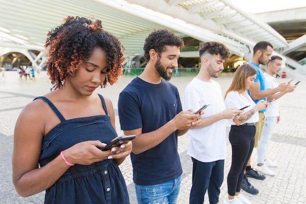 Línea de personas mixtas compitiendo mensajes de texto en teléfonos inteligentes