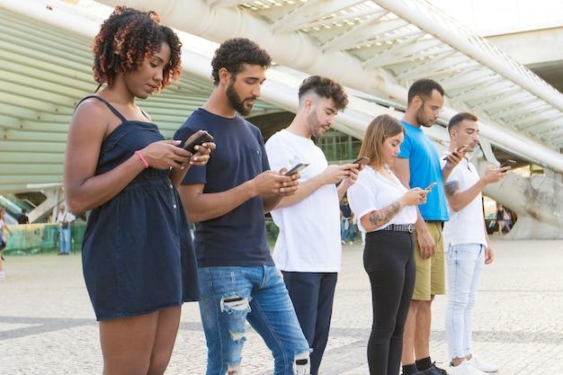Línea de personas navegando por internet en teléfonos inteligentes fuera
