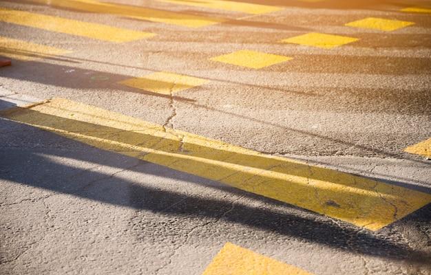 Línea de pintura amarilla en la textura de la superficie de la carretera de asfalto negro