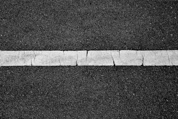 Línea de pintura blanca sobre asfalto negro. fondo de transporte espacial