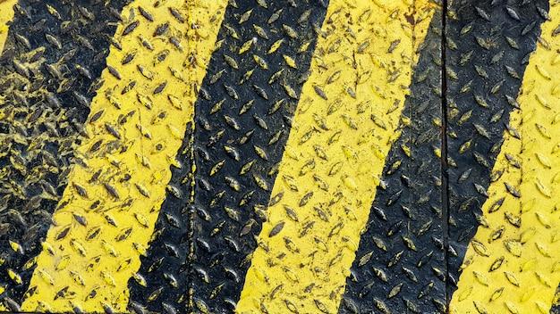 Línea de pintura negra y amarilla sobre fondo texturado de metal antideslizante