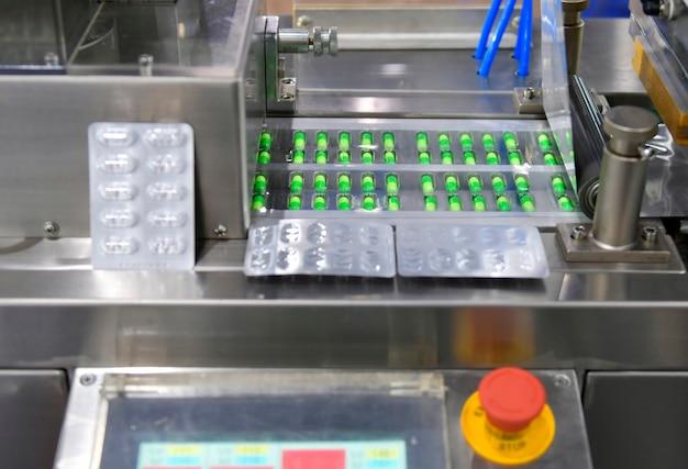 Línea de producción de píldoras de medicina cápsula verde, concepto farmacéutico industrial
