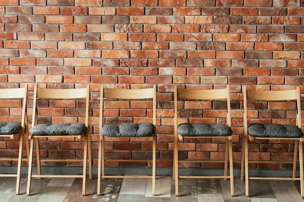 Línea de sillas vacías en el desván de la pared de ladrillo. asiento libre. concepto de sala de espera o sesión de entrevista de trabajo. competencia rivalidad y promoción.