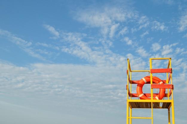 Línea de vida naranja en torre de salvavidas amarilla sobre fondo de cielo azul