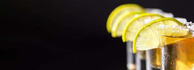 Línea de vista frontal de tragos de tequila dorado con espacio de copia