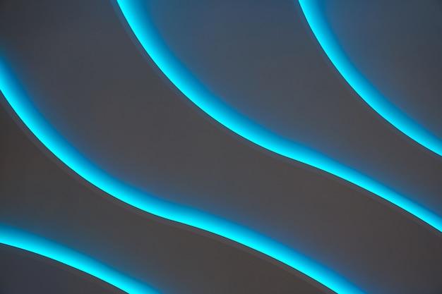 Líneas curvas de luz de fondo azul sobre un fondo oscuro