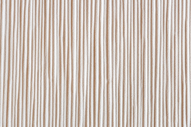Líneas definidas verticalmente en una pared granulada.