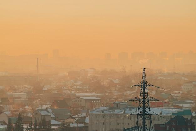 Líneas eléctricas en la ciudad al amanecer. siluetas de edificios urbanos entre el smog en la salida del sol. cables de alta tensión en el cálido cielo amarillo anaranjado. industria energética al atardecer. fuente de alimentación de la ciudad. niebla de fondo urbano.