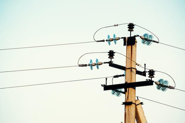Líneas eléctricas en el fondo de primer plano del cielo azul. eje eléctrico en poste. equipos de electricidad con copyspace. cables de alta tensión en el cielo. industria de la electricidad.