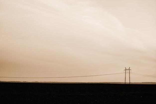 Líneas eléctricas en el fondo de primer plano del cielo. silueta de poste eléctrico con copyspace en tonos sepia. cables de alta tensión sobre tierra. industria eléctrica en monocromo.