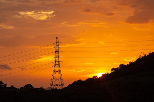Líneas eléctricas de transmisión de electricidad al atardecer, torre de alta tensión.