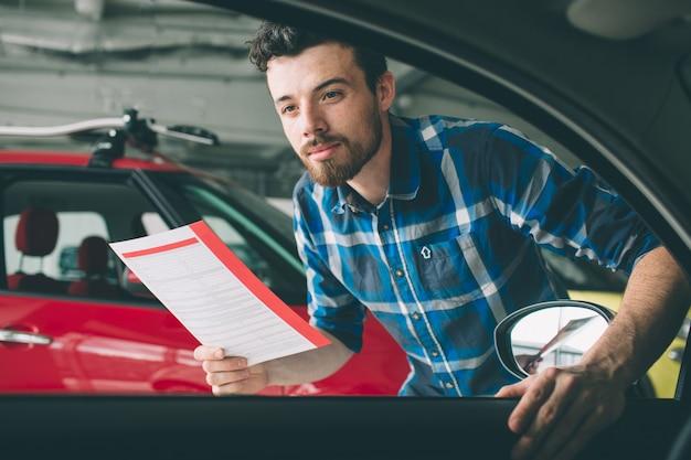Líneas perfectas el joven barbudo de cabello oscuro examinando el auto en el concesionario y haciendo su elección. retrato horizontal de un joven en el coche. está pensando si debería comprarlo.
