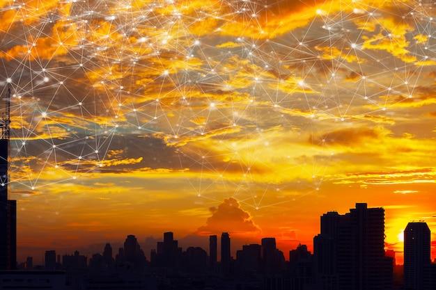 Líneas y puntos como iconos de tecnología de conexión inalámbrica en el cielo sobre la ciudad al atardecer.