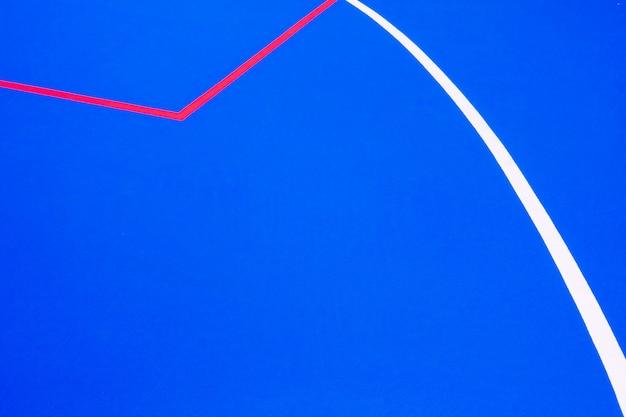 Líneas rojas que cruzan un piso pintado de azul de color intenso para usar como fondo de diseño minimalista.