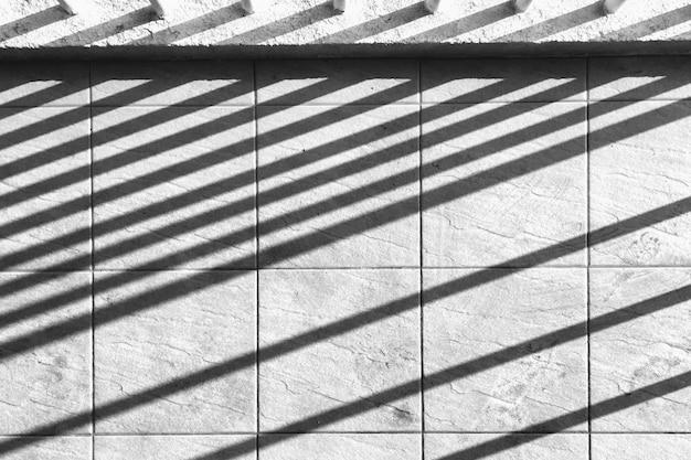 Líneas de sombra perpendiculares en muro de hormigón.