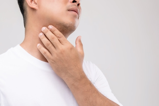 Linfoma en concepto de hombres: retrato de hombre asiático está tocando su cuello en la posición de los ganglios linfáticos.