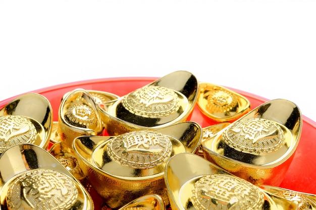 Lingotes dorados en bandeja roja aislados en blanco. idioma chino en lingotes significa